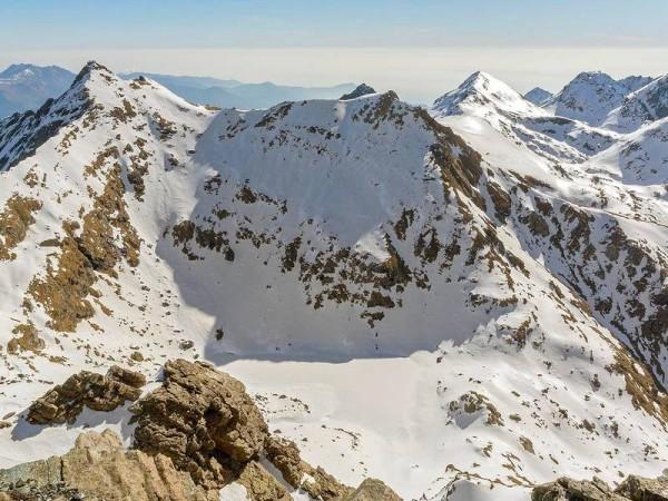 Vue sur lac enneigé depuis le sommet - alpinisme hivernal